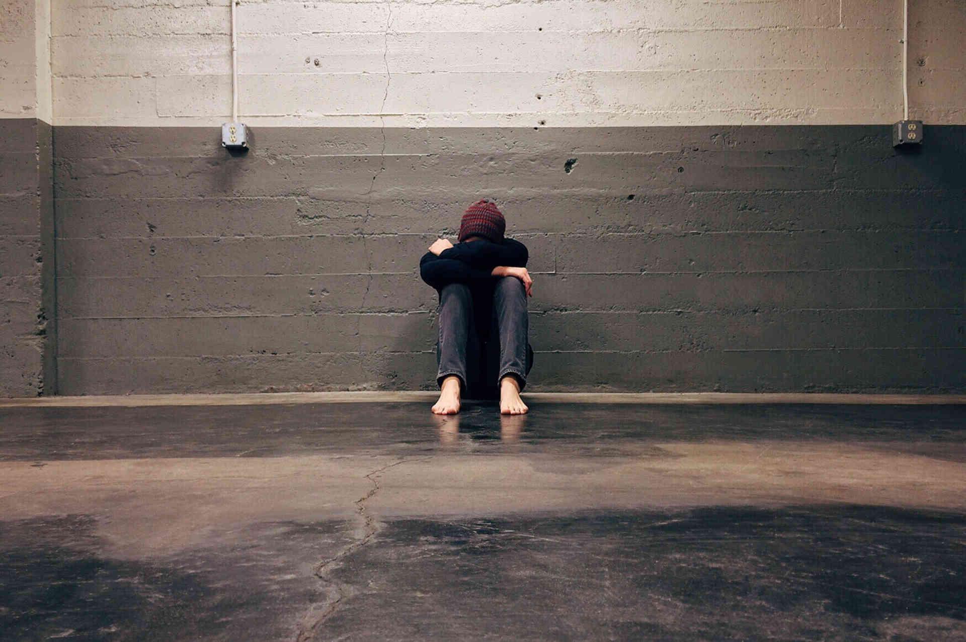 mann sitzt auf dem Boden und ist traurig